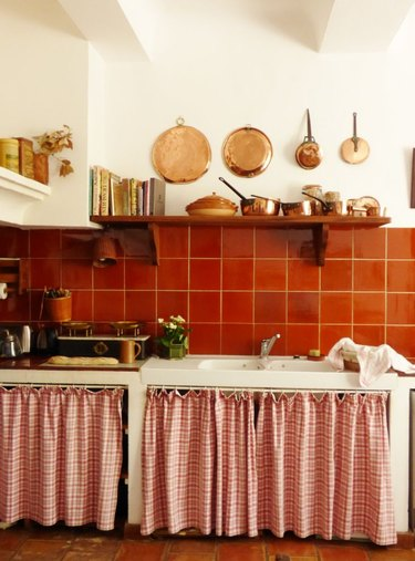 Kitchen with bright orange backsplash, copper pots, open shelving and patterned cabinet curtains.