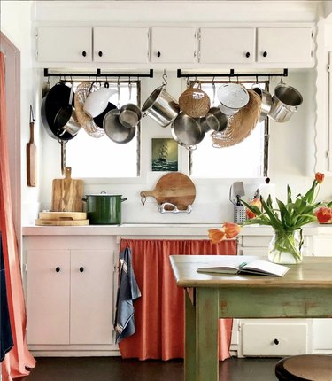 White kitchen with bright colored cabinet curtain and hanging pots.