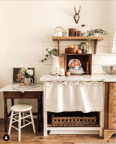 Farmhouse kitchen with shiplap backsplash and a half curtain hanging under the counter.