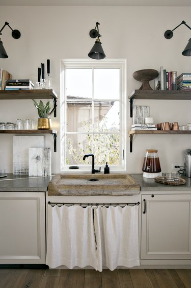 White and black kitchen with white curtains instead of cabinet doors under sink.