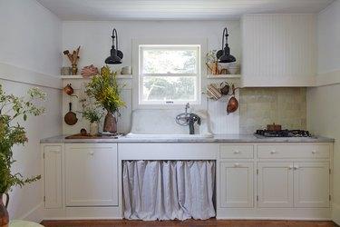 White farmhouse kitchen with linen curtains under sink.