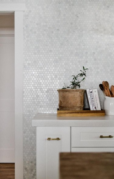 concrete countertop with tile backsplash and white cabinets