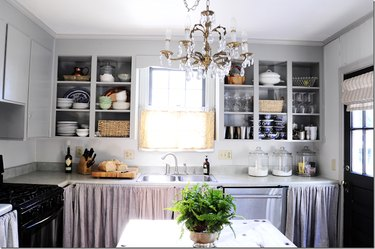 Neutral gray kitchen with chandelier and open cabinets.