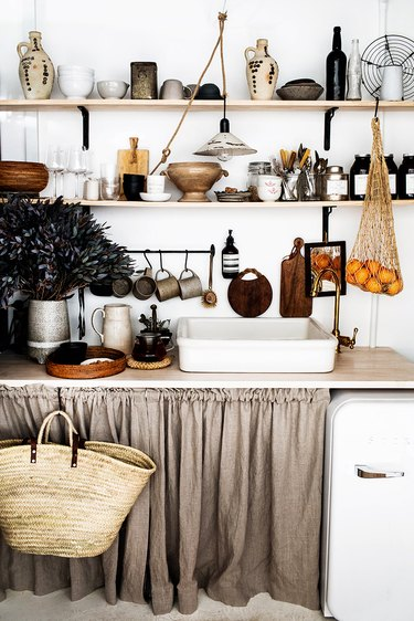 Rustic kitchen with open wood shelves and linen curtains under the counter.