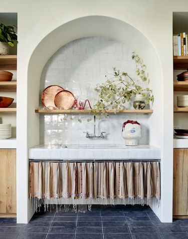 European style kitchen with blue tile floors and tasseled curtains under sink.