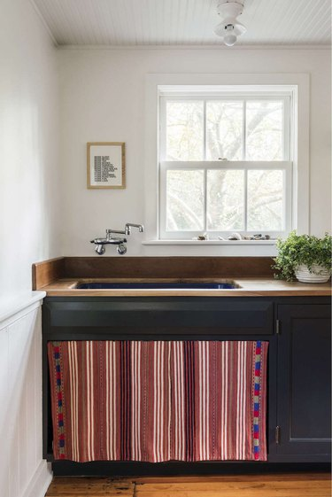 Kitchen with dark lower cabinets and vintage tapestry under the sink.