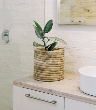 woven planter on a counter near sink and drawers