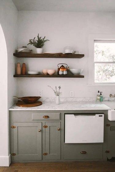 sage green kitchen with brass hardware