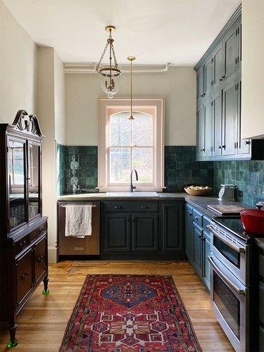 dark traditional kitchen with vintage rug and green tile backsplash