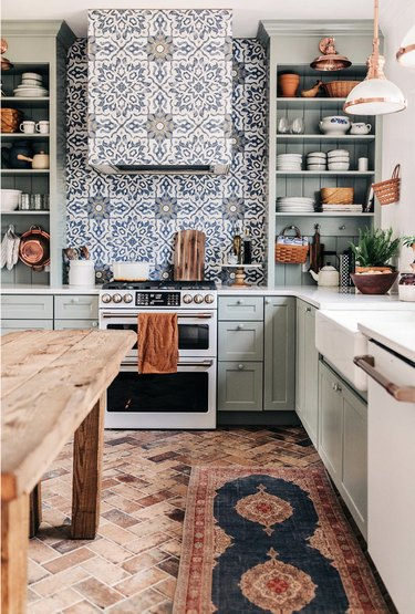 sage green kitchen with painted gray knobs