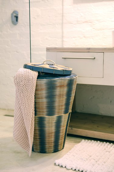 blue recycled PVC laundry basket in natural and blue colors near sink with drawers
