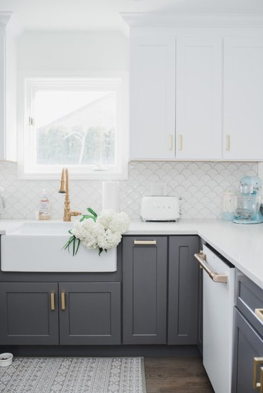 white and gray kitchen with brass hardware