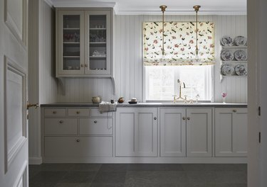 traditional kitchen with beadboard wall paneling and Roman shade window covering
