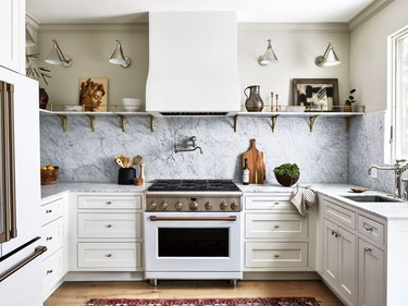 traditional kitchen with marble backsplash and open shelving for art