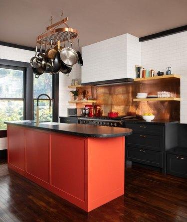Orange kitchen island with copper backsplash