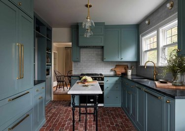 blue kitchen with black countertops and marble island