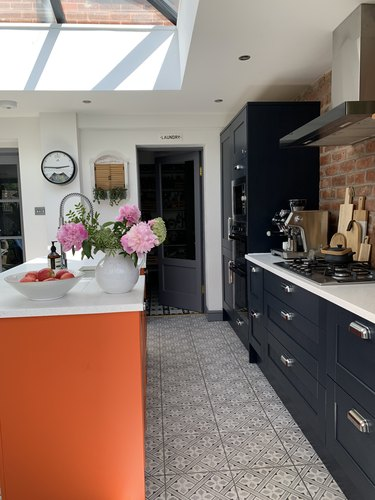 Kitchen with orange island and navy cabinets