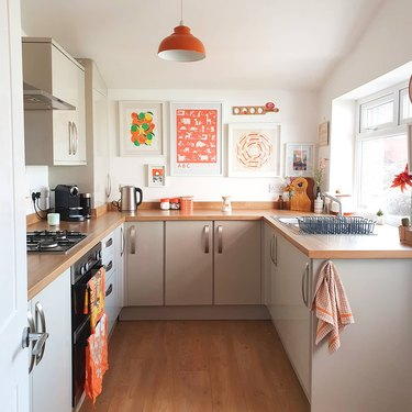 Kitchen with orange accessories and artwork