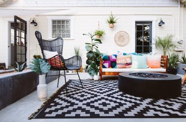 Patio with gas fire pit, chair, pillows, outdoor rug