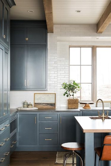 blue inset kitchen cabinets and wooden beams