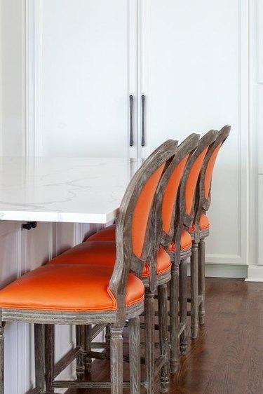 Orange bar stools in kitchen