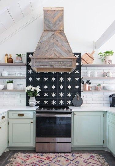 mint green kitchen cabinets with patterned tile backsplash