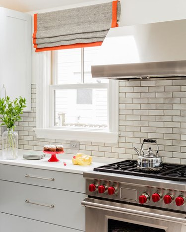 Kitchen with orange trimmed window treatments