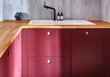 Red kitchen cabinets with wood counters