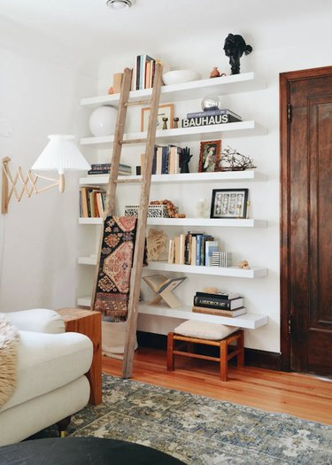 Neutral color palette library wall with floating shelves