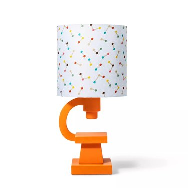 orange lamp with multicolored lamp shade, base is orange in the shape of a microscope