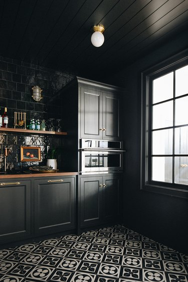 black kitchen with pattern floor tiles and open shelving