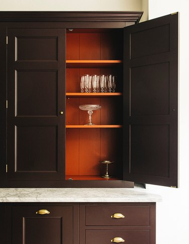 Kitchen cabinets with orange painted on the inside