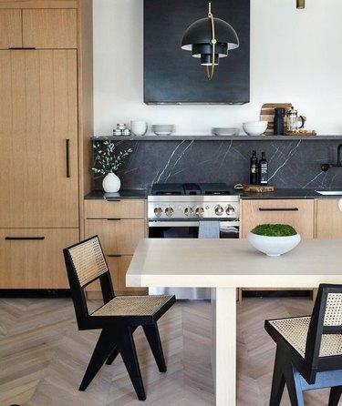 pale wood kitchen with black soapstone backsplash and chevron floors