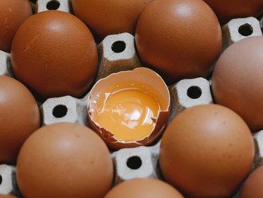 open brown egg in carton