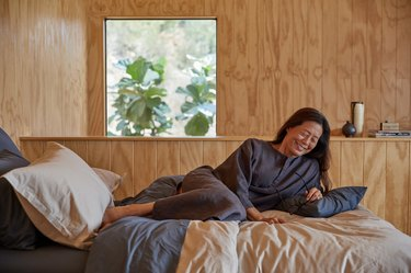 woman wearing parachute linen house dress on bed