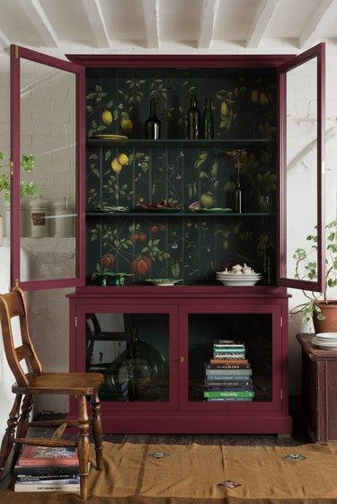 Dark maroon kitchen cabinet, chair, books, plates
