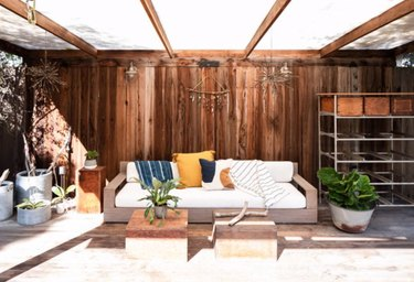 Deck with pergola, couch, plants, coffee table