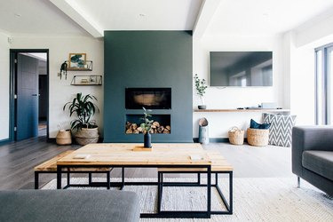 Minimalist living room with accent color fireplace and stacked logs.