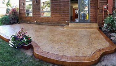 A brown concrete stamped patio with a bronze borer