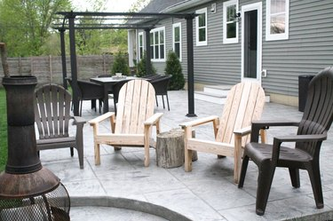 A multi-level stamped concrete patio with a chiminea and patio chairs