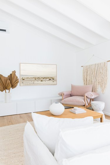 Bright living room with white walls and a white couch, a large macrame wall hanging and pink oversized arm chair.
