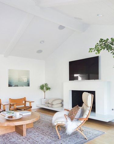 White walled living space with white fireplace and green plants.