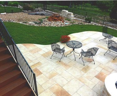 A light tan shaded stamped concrete patio in a backyard with green grass and several patio chairs