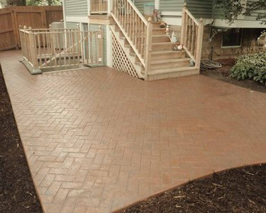 A herringbone patterned stamped concrete patio below a stairwell