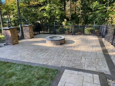 A stamped concrete patio with a dark border, featuring a fire pit in the center