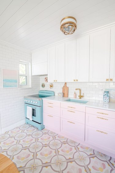 pink and white kitchen with brass hardware