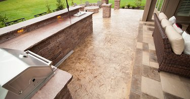 An outdoor kitchen with a brown stamped concrete floor