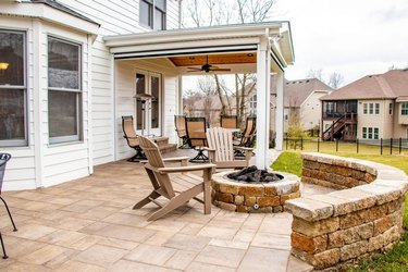 A stamped concrete patio with a brick half wall and a matching brick fire pit