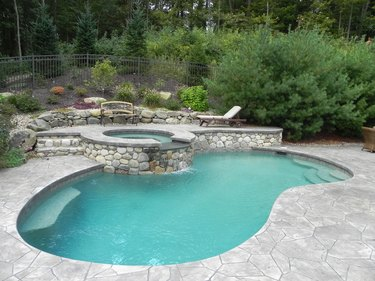 A freeform pool surrounded by a light gray stamped concrete patio