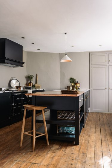 English country kitchen with black cabinets and wood flooring